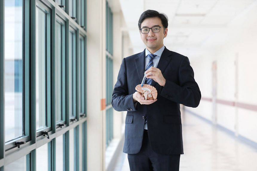 National Neuroscience Institute neurosurgery research director Nicolas Kon with a BrainPath obturator (blue) inside a sheath (transparent) and a model of the brain. It took him a year of trying before he succeeded in bringing the method to Singapore.
