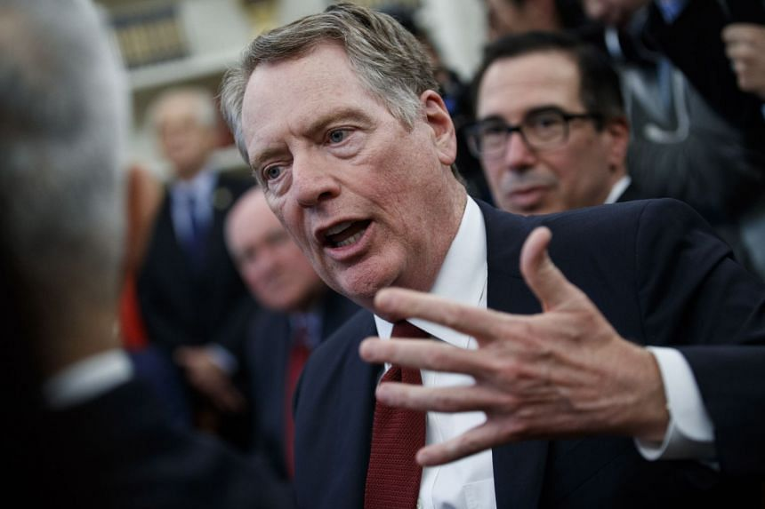 US Trade Representative Robert Lighthizer (centre) responds to a question from the news media during a meeting in the Oval Office of the White House.