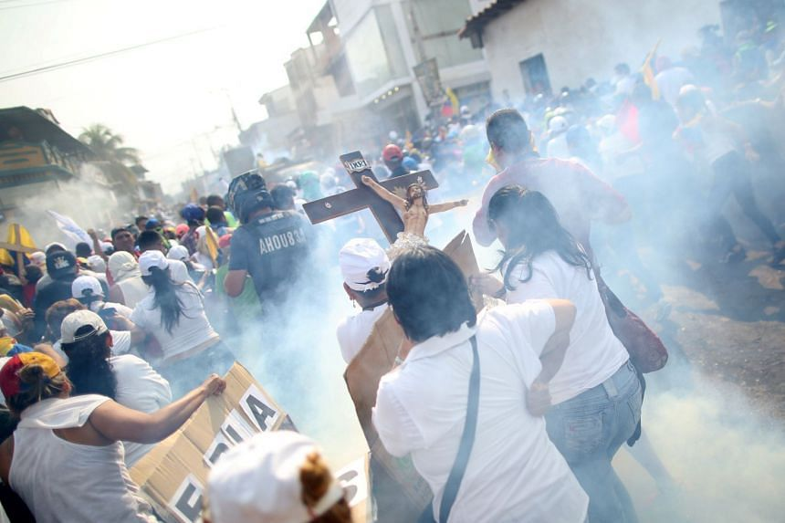 Demonstrators carry a crucifix while clashing with security forces in Urena, Venezuela.