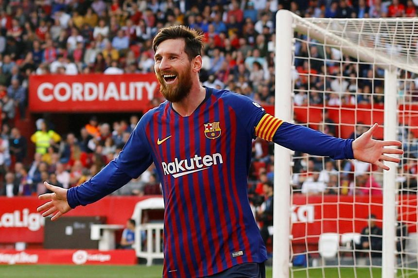 Messi celebrates scoring Barcelona's third goal against Seville to complete his hat-trick.