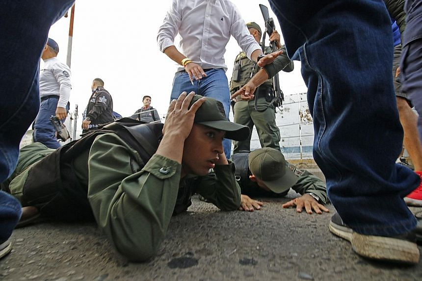 Venezuelan soldiers being held after driving into Colombia from the Venezuelan side of the Simon Bolivar International Bridge in Cucuta yesterday. President Nicolas Maduro's government has closed bridge crossings on the frontier being used by protest