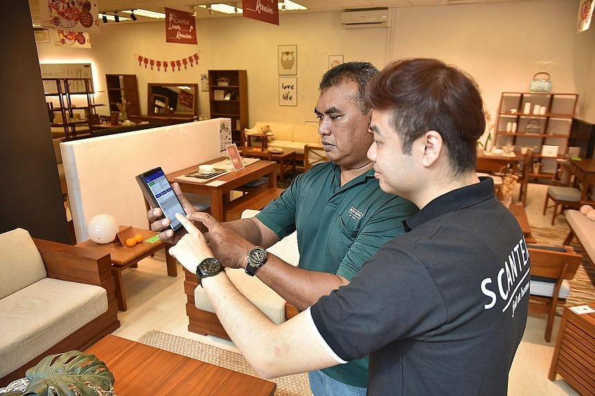 A manager and delivery man checking the routes on the delivery automation application at the Scanteak furniture showroom in Sungei Kadut. It used to take staff at the furniture retailer around two hours a day to plan the routes. The adoption of the a