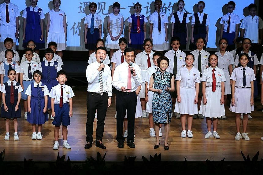 Mr Ong Ye Kung (centre) reciting a Chinese poem with Mr Baey Yam Keng and Ms Low Yen Ling at the launch of a book commemorating the 40th anniversary of SAP schools yesterday.
