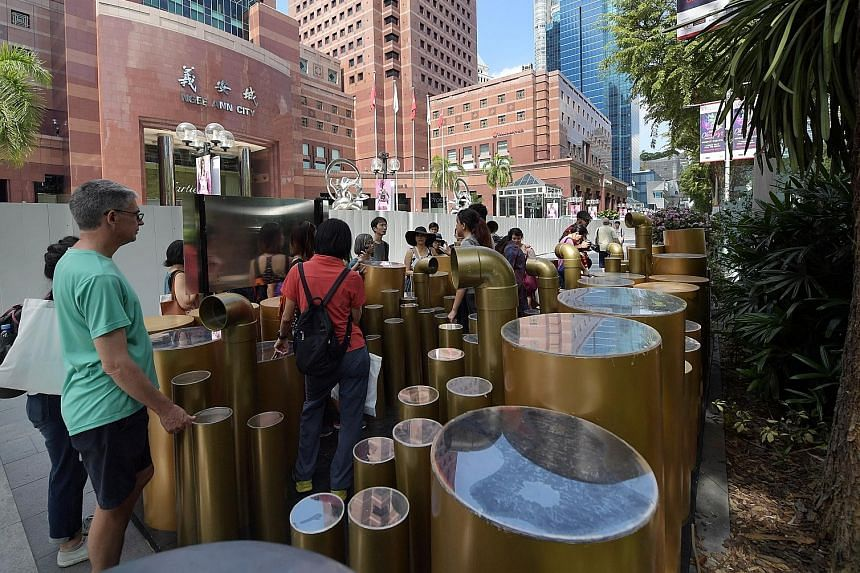 The first of three two-hour walking tours in the Orchard Road area was held yesterday. Here, the group is viewing an art installation outside Ngee Ann City mall titled Orchard: A Stroll Between Valleys.
