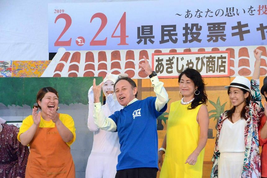 """Okinawa Governor Denny Tamaki attends a meeting in Naha, on Feb 23, 2019. He has urged residents to turn out and cast their """"precious votes"""" in the poll."""