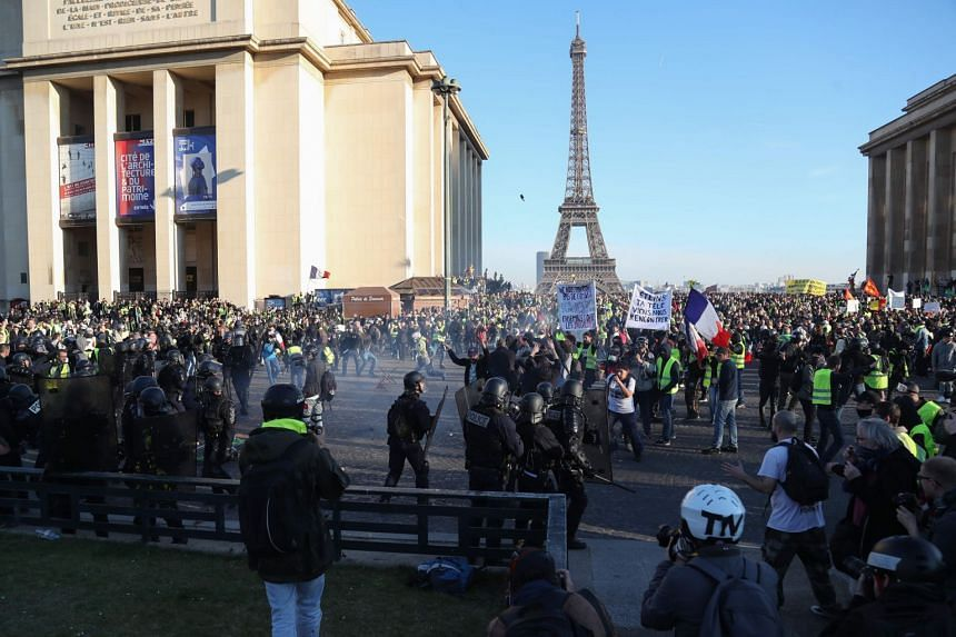Protesters clash with police in front of the Eiffel tower on Trocadero Plaza in Paris.