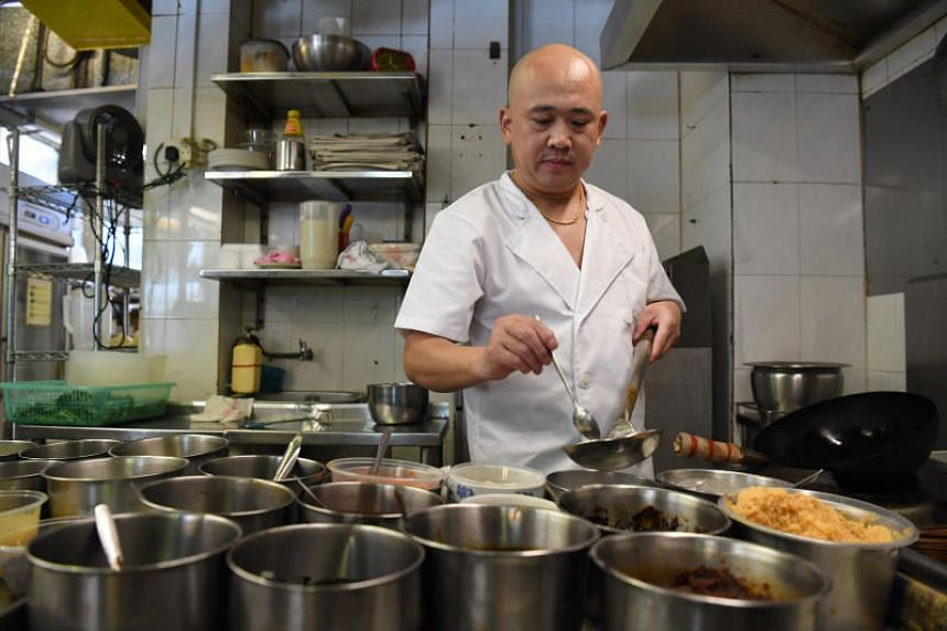 Mr Zhu Shenggang, a chef at Mak's Place - The Hawkerant at Changi. On weekends, the eatery's owner has to roll up his sleeves and be cook and cleaner due to a lack of staff.