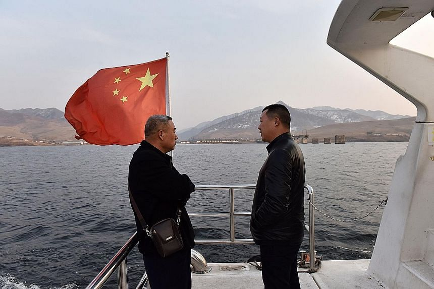 A Chinese tourist boat plying the Yalu river yesterday. North Korea can be seen in the background. North Korean leader Kim Jong Un is scheduled to meet US President Donald Trump for their second summit in Hanoi this week.