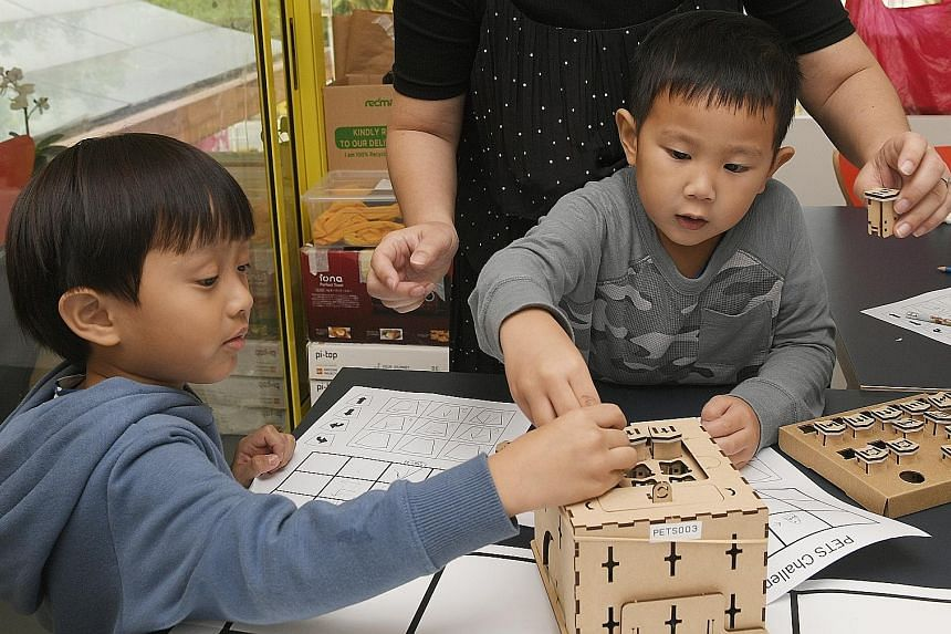 """Avery Woo Jia Nui (left) and Connor Lee Cher Yee, both four, are taking part in a coding programme at Saturday Kids coding school titled """"Curious Cubs: Explore the Wonders of Tech"""". The children are coding and learning how to operate PETS, a friendly"""