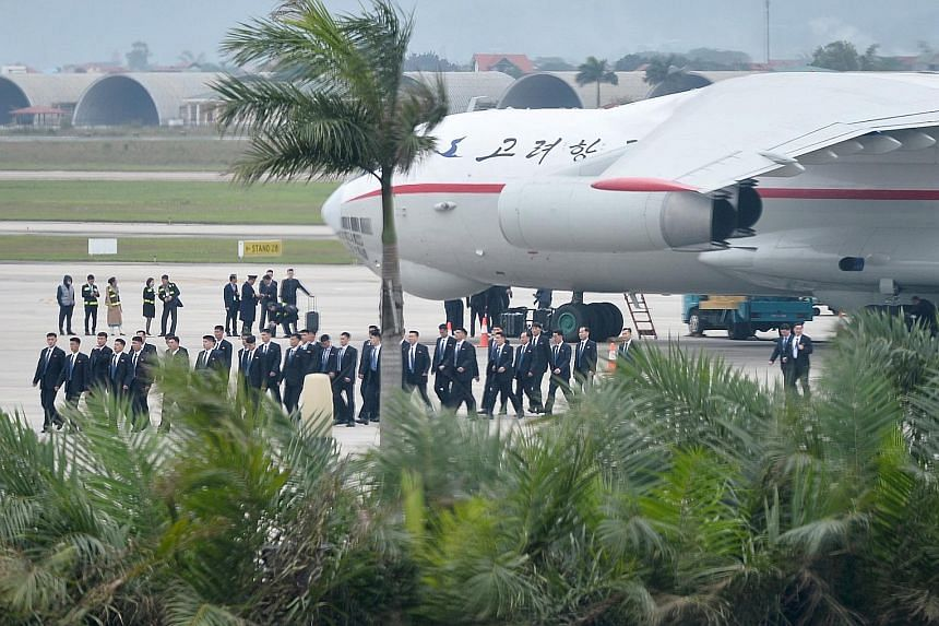 Above: Some 100 bodyguards for North Korean leader Kim Jong Un arriving yesterday at Noi Bai International Airport in Hanoi, Vietnam, on a North Korean cargo plane ahead of the summit. Right: Mr Kim Jong Un (centre) being sent off by his top official