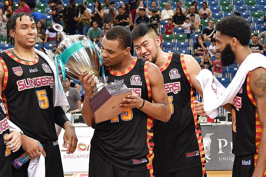 Xavier Alexander kissing the Straits Cup after the Slingers beat the Dragons 81-44, as (from left) John Fields, Delvin Goh and Jerran Young join in the celebrations.
