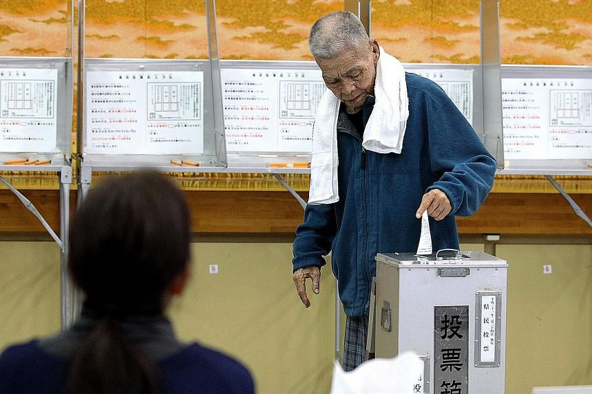 An Okinawa resident voting yesterday on the relocation of US Marine Corps Air Station Futenma to a newly planned base in the coastal Henoko district. The referendum is merely symbolic and Prime Minister Shinzo Abe has said Tokyo would ignore the outc