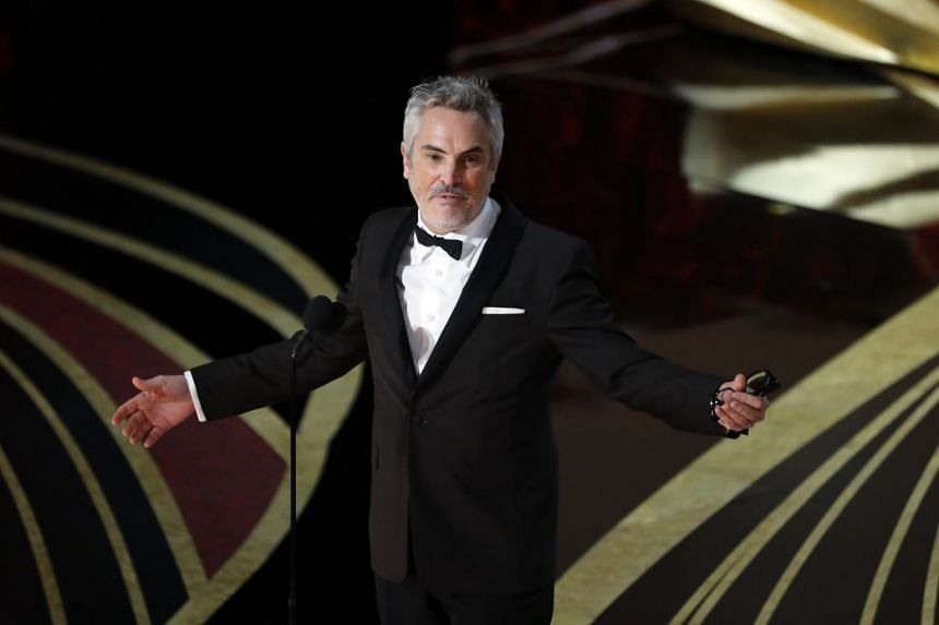 Alfonso Cuaron speaking on stage after accepting the Best Director award for Roma at the Academy Awards.