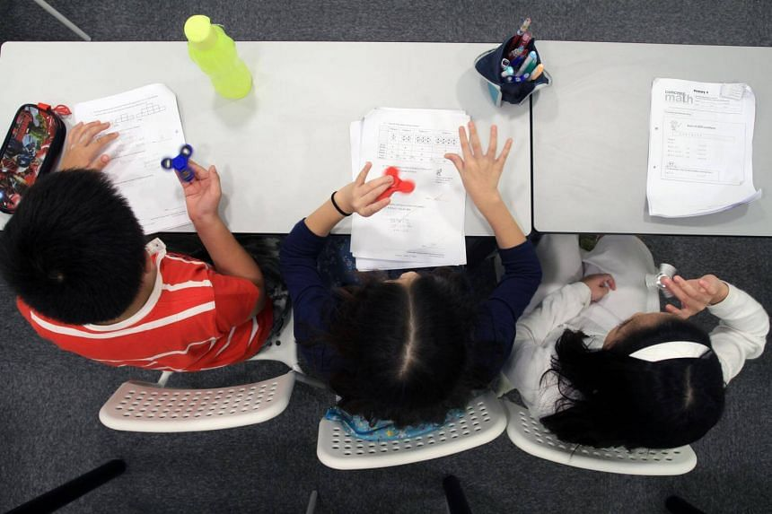 Posed photo of children playing with fidget spinners in a classroom.