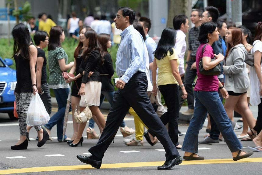 Office workers and pedestrians crossing the road at Raffles Place.