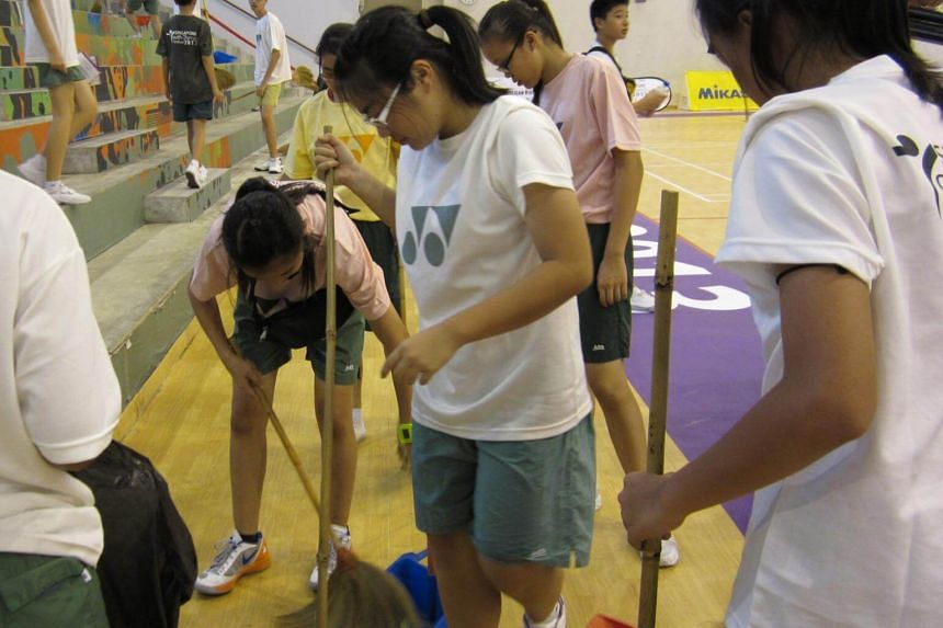 A student volunteer sweeping the floor of an indoor sports hall.