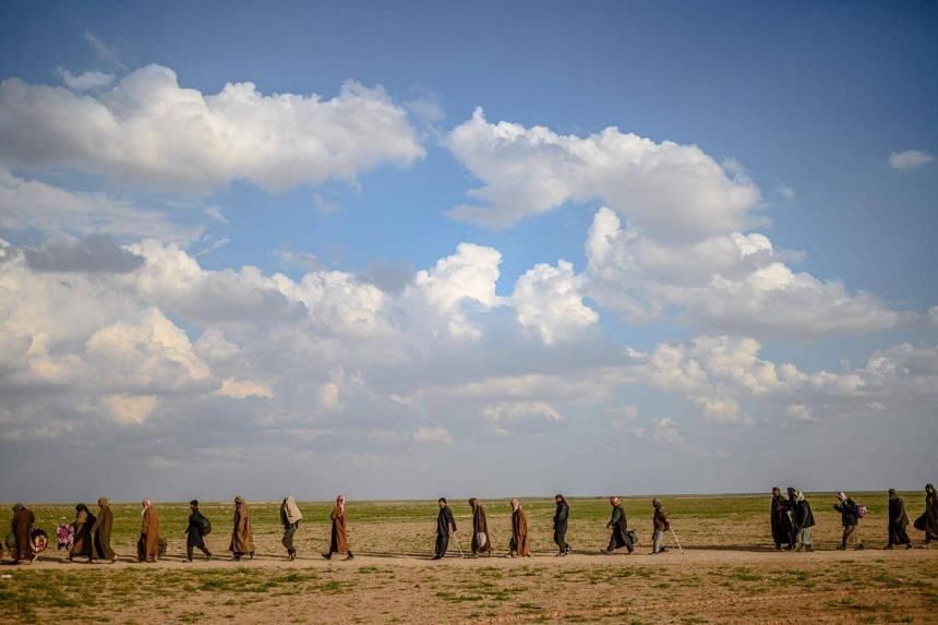 Men walk towards an area controlled by fighters of the US-backed Syrian Democratic Forces, after leaving Baghouz, Syria, on Feb 22, 2019.