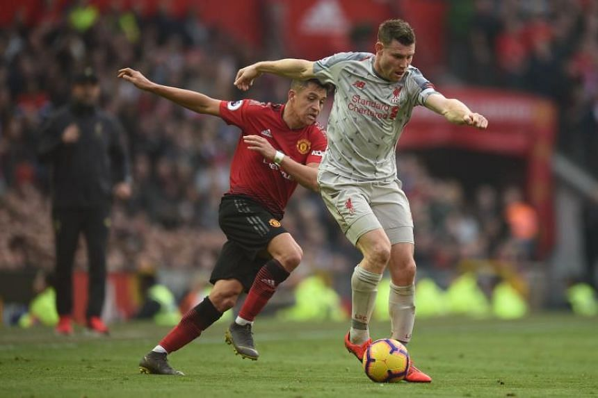 Manchester United's Chilean striker Alexis Sanchez (left) chases Liverpool's English midfielder James Milner during the EPL match between Manchester United and Liverpool at Old Trafford in Manchester, north west England, on Feb 24, 2019.
