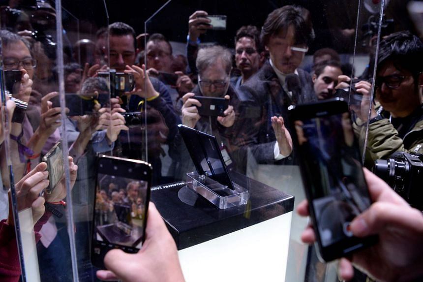 Visitors taking photos of Huawei's new foldable 5G smartphone, the Mate X, at the Mobile World Congress, on Feb 24, 2019, in Barcelona.