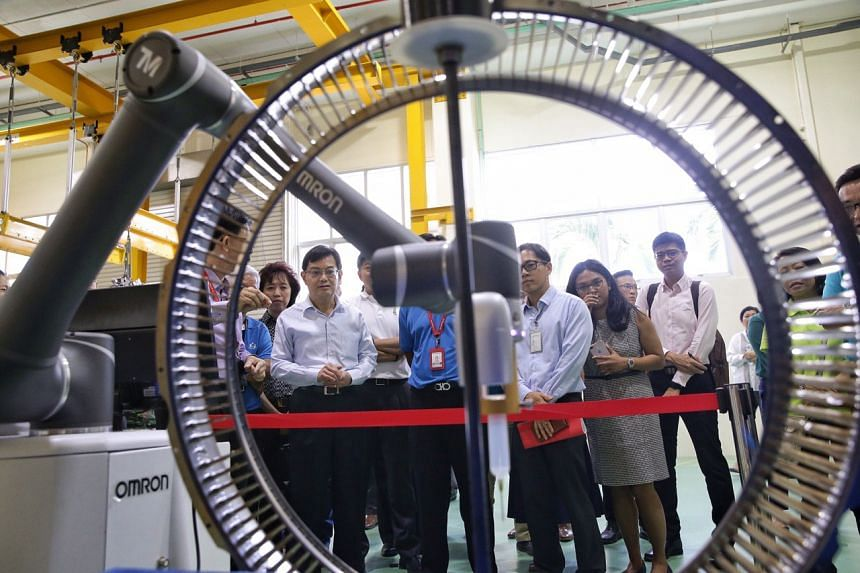 Finance Minister Heng Swee Keat (fourth from left) watches as a robot (the arm structure) works on a booster vane assembly during his tour of ST Engineering's aerospace facility.