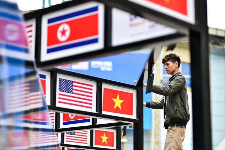 A man fixes the electric line next to pictures of Vietnam, US and North Korean national flags in Hanoi on Feb 25, 2019, ahead of the second US-North Korean summit.