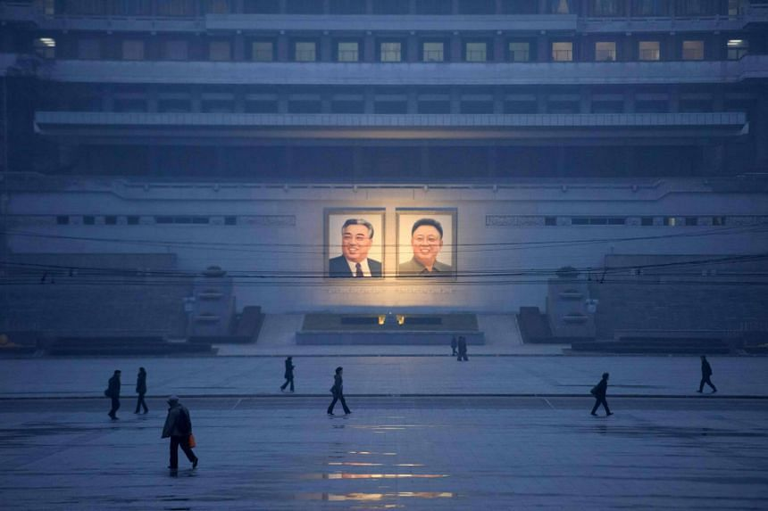 Pedestrians walking past portraits of late North Korean leaders Kim Il Sung and Kim Jong Il in Pyongyang, on Dec 3, 2018.