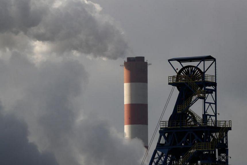 Chimney of Laziska Power Station, a thermal power plant, is seen behind Boleslaw Smialy Coal Mine in Laziska Gorne, Poland, on Dec 5, 2018.