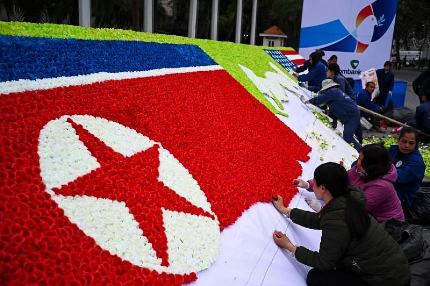 Workers make a North Korean and a US flag out of paper-flowers beside a street in Hanoi on Feb 25, 2019, ahead of the second US-North Korea summit.