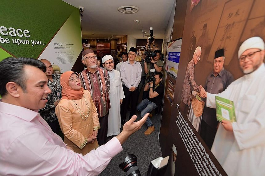 Religious Rehabilitation Group (RRG) vice-chairman Mohamed Ali (left) showing President Halimah Yacob and her husband, Mr Mohamed Abdullah Alhabshee, around the RRG resource and counselling centre at the Khadijah Mosque during their visit yesterday.