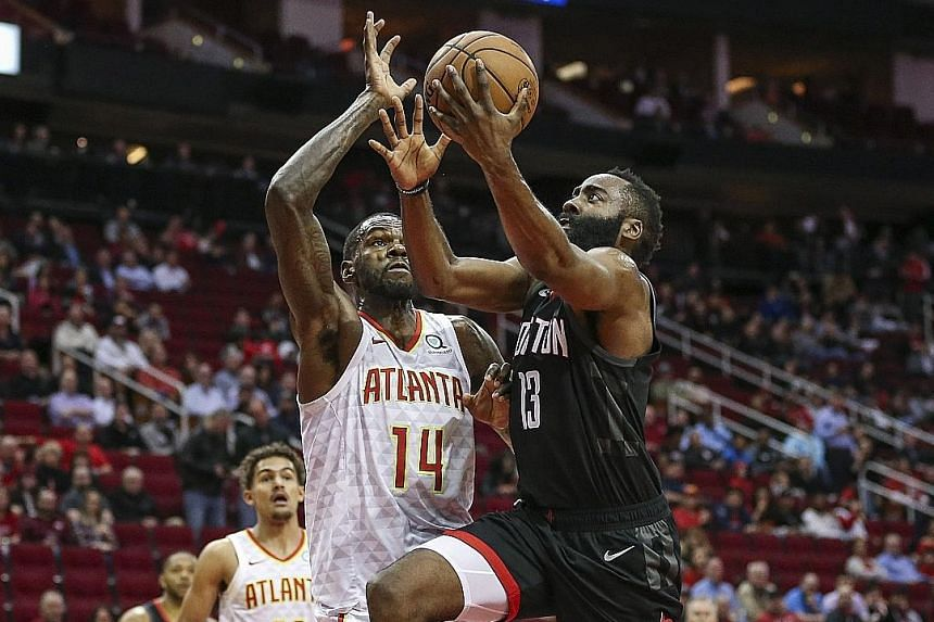 Houston Rockets guard James Harden driving past Atlanta Hawks centre Dewayne Dedmon to score in their National Basketball Association game at the Toyota Centre on Monday night. Harden finished with 28 points in the 119-111 win, despite missing all 10