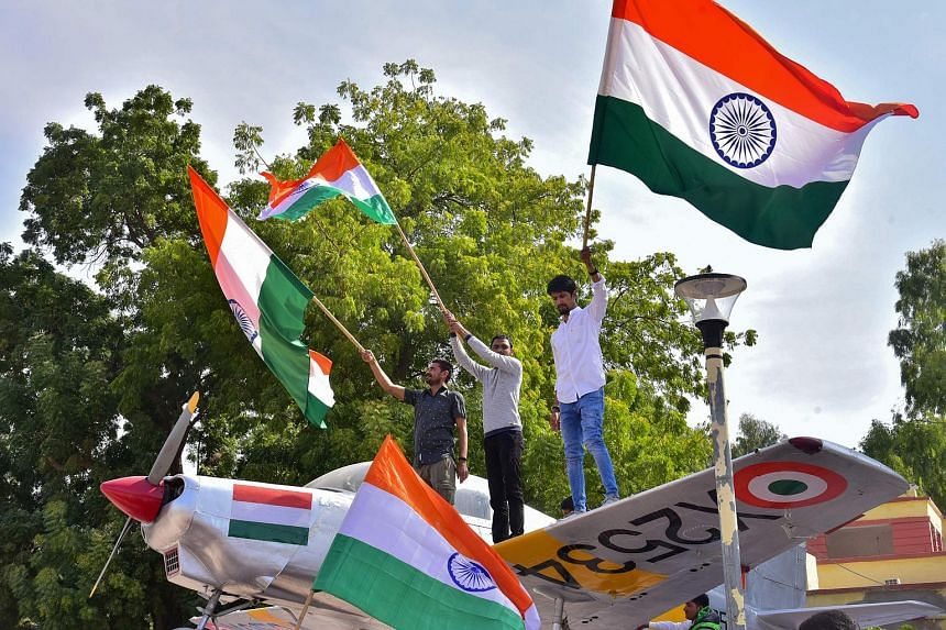 Indian residents hold flags on a model of a military plane to celebrate the Indian Air Force strike launched on a Jaish-e-Mohammad camp at Balakot, on Feb 26, 2019.