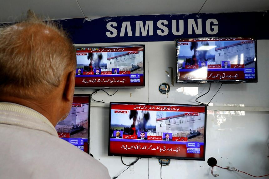 A man looks at television screens at a shop in Karachi, after Pakistan shot down two Indian planes on Feb 27, 2019.