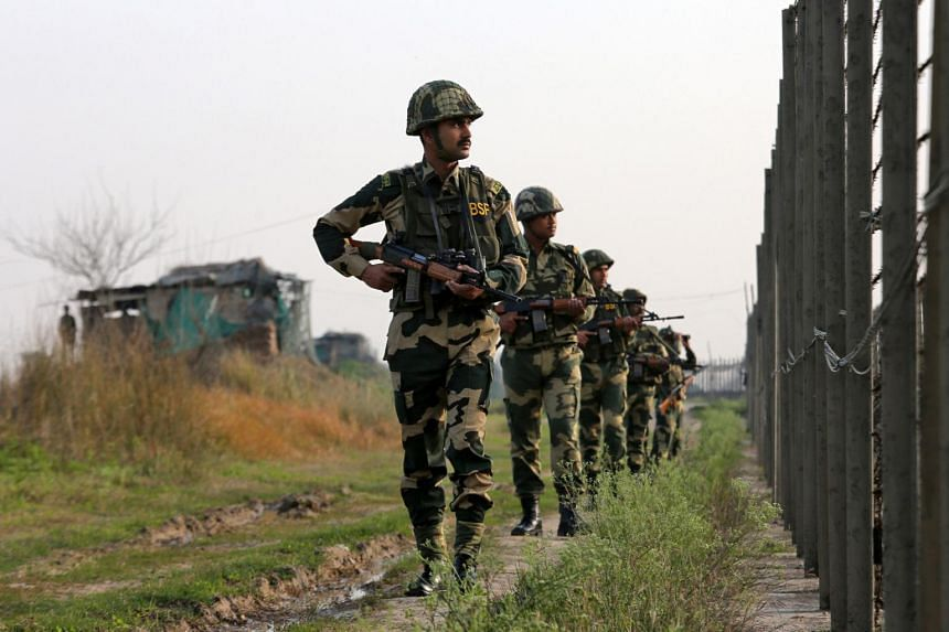 India's Border Security Force soldiers patrol along the fenced border with Pakistan in Ranbir Singh Pura sector near Jammu, on Feb 26, 2019.