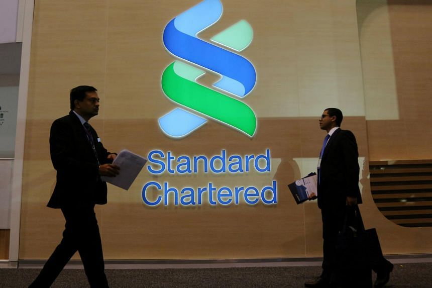 People pass by the logo of Standard Chartered at the SIBOS banking and financial conference in Toronto, Ontario, Canada, on Oct 19, 2017.