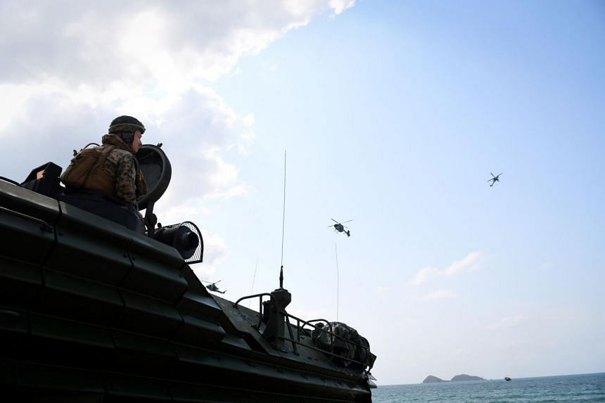 A US Marine watches from an amphibious assault vehicle as helicopters fly during a military exercise on Feb 16, 2019.