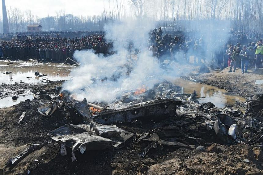 Indian soldiers and Kashmiri onlookers stand near the remains of an Indian Air Force aircraft after it crashed in Budgam district on Feb 27, 2019.