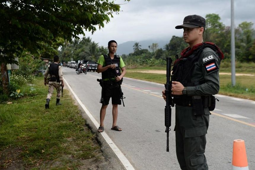 Armed Thai police personnel secure the area where authorities recovered the bodies of a Buddhist and a Muslim policemen in the restive southern Thailand province of Narathiwat on Feb 27, 2019.