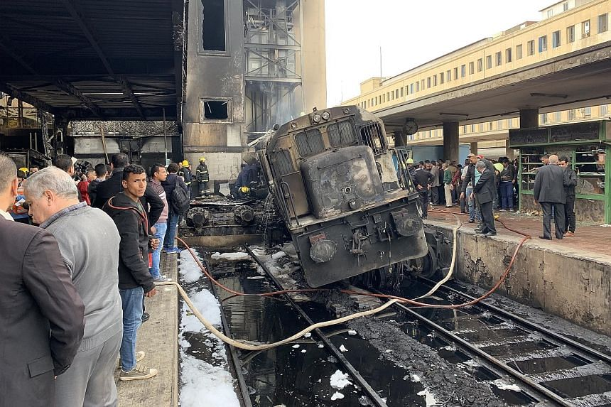 Left: People surveying the charred engine of the train which crashed through the buffers at the main train station in the Egyptian capital Cairo yesterday. Below: A man amid the debris at the scene of the accident.