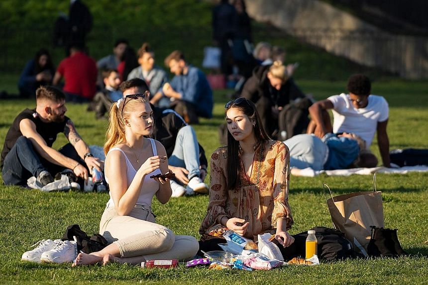 People basking in the sun at Green Park, central London, on Tuesday as Britain experienced record temperatures for a winter month for the second consecutive day.