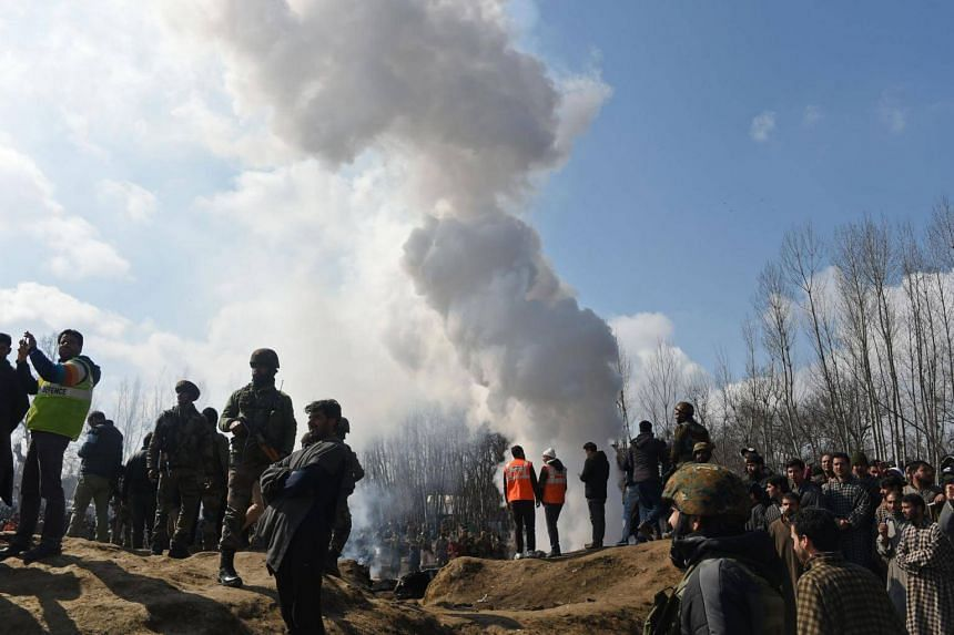 Indian soldiers and Kashmiri onlookers stand near the remains of an Indian Air Force helicopter after it crashed in Budgam district, outside Srinagar, on Feb 27, 2019.