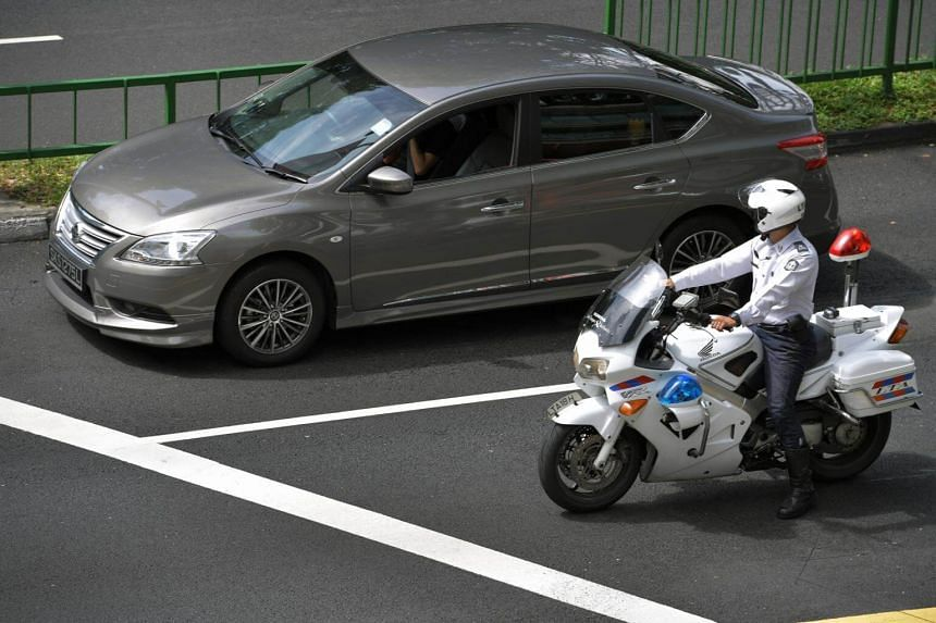 A traffic policeman checking on a car at a traffic light along Toa Payoh Lorong 2.