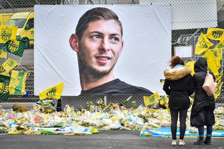 People look at flowers displayed in front of a portrait of Sala at the Beauvoir stadium in Nantes.