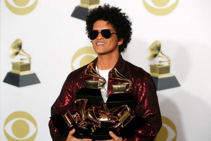 Bruno Mars holding Grammys that he won in 2018 at the 60th Annual Grammy Awards.