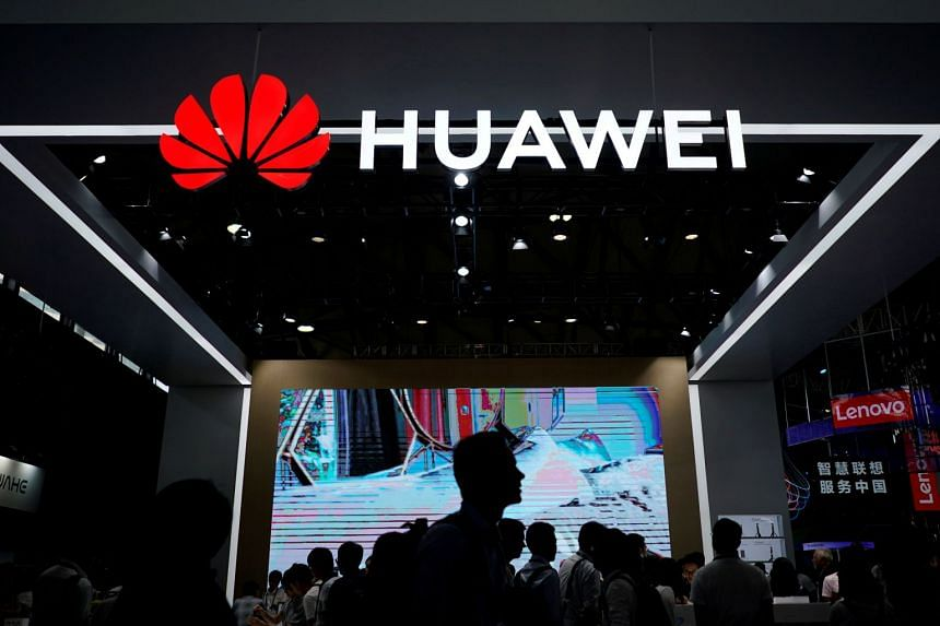 People walk past a Huawei signboard at CES Asia in Shanghai, in 2018.