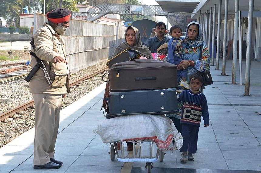Pakistanis left stranded yesterday following the suspension of the rail service between Delhi and Attari in India and Lahore in Pakistan. Kashmiris fleeing the border town of Chakothi on Wednesday. Left: Children with banners and Indian national flag