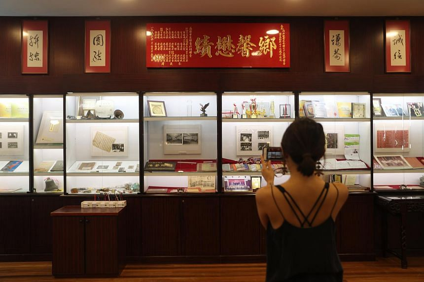 A woman takes a photo of a display at the Chin Kang Huay Kuan.