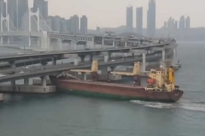 The upper superstructures of a container ship is seen colliding with the bridge.