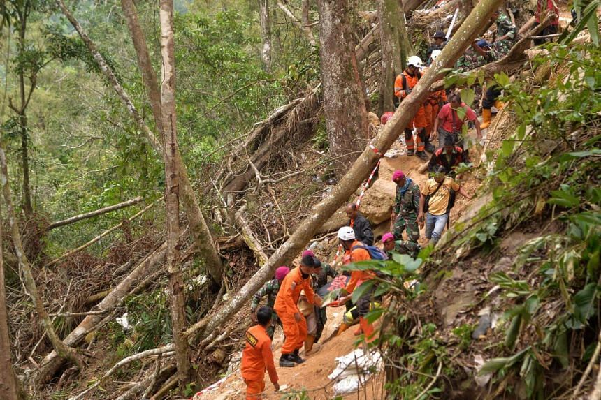 Members of an Indonesian search and rescue team carry a survivor after a mine collapsed in Bolaang Mongondow, North Sulawesi, on Feb 28, 2019.