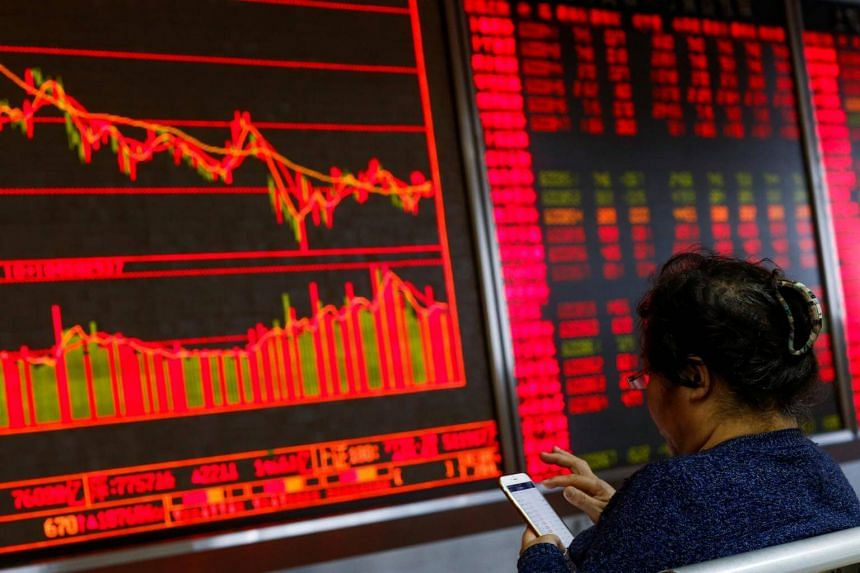 An investor sits in front of a board showing stock information at a brokerage office in Beijing, China.