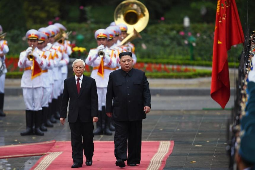 North Korea's leader Kim Jong Un (right) and Vietnam's President Nguyen Phu Trong inspect a ceremonial guard of honor during a welcoming ceremony at the Presidential Palace in Hanoi, Vietnam, on March 1, 2019.